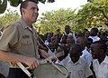US Navy 100119-N-8463W-003 Musician 3rd Class Zach Gormley, assigned to the U.S. Naval Forces Europe Band, performs for children at the Msimbazi Mseto Primary School in Dar Es Salaam.jpg