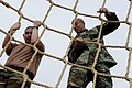 US Navy 110316-N-KK330-369 Chief Special Warfare Operator David Goggins climbs the cargo net obstacle with a Make-A-Wish Foundation recipient.jpg
