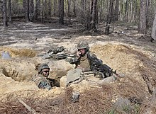 US Navy 110330-N-7716W-003 Chiefs and officers man an M-240B machine gun and M-16 rifle in a fox hole on the defensive line during a joint chief an.jpg