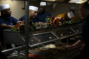 US Navy 111225-N-DR144-131 Chief petty officers serve Christmas dinner to junior enlisted Sailors on the mess decks aboard the Nimitz-class aircraf.jpg