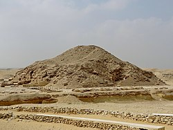 A ruined mass of bricks, sand and rocks resembling an earthen mound