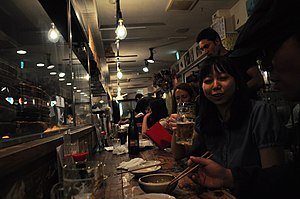 Izakaya - People at an izakaya, sitting by the bar and facing the kitchen.