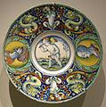 Urbino, venezia o pesaro maiolica, piatto con un putto alato a davcalcioni di un bastone.JPG
