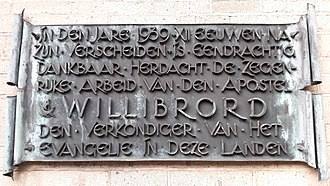 Roman Catholic Archdiocese of Utrecht - commemoration plaque at the Domkerk in Utrecht. Translation: In the year 1939, twelve centuries after his death, the blessed work of the apostel Willibrord, the preacher of the Gospel in these lands, is unitedly and thankfully commemorated.