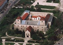A castle with a large courtyard, a fortified entrance and two towers