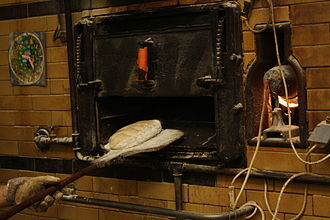 Peel (tool) - A loaf of bread being placed into an oven with a wooden peel (the baker also wears a glove as a shield from the heat)