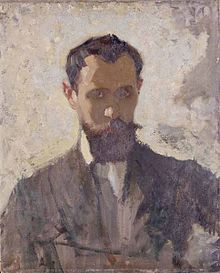 A head and shoulders portrait of a thirty something man, with a dark beard, facing towards the viewer