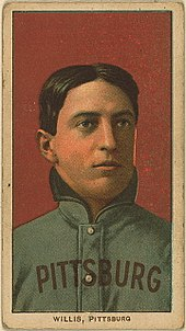 A color baseball card; pictured is a man in a heavy Pittsburgh uniform with his collar turned up