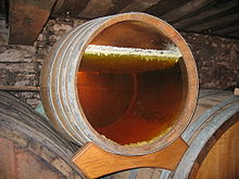 Photo showing a barrel with a glass bottom revealing the layer of yeast on the surface under which the yellow wine is ageing. This yeast is in the form of an irregular white layer - it forms small stalactites that sink a few millimetres into the wine which is already dark yellow wine.  The wall in the background is grey, probably coated in grey mould.