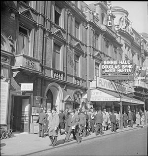 "Douglas Byng - August 1943: ""Actor Douglas Byng (centre, just stepping onto the pavement) arrives for work at the Lyric Theatre, where he is starring in 'Flying Colours' with Binnie Hale and Jackie Hunter."""