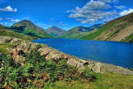 بحيرة زرقاء واقعة بين تلال خضراء.