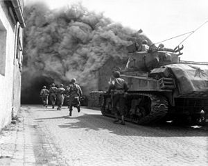 United States Army soldiers supported by a M4 Sherman tank move through a smoke filled street in Wernberg, Germany during April 1945