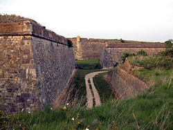 Photo shows a stone-faced fortress wall 20 to 30 feet high on the left. To the right is a stone wall 10 feet high. In between is a low area with a trail.