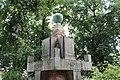 12.Ondřejov pomník padlým detail vrcholu pomníku letopočtem MCMXXVIII a letopočtem MCMXXVIII šikmý pohled z úrovně trávníku pře keře.JPG