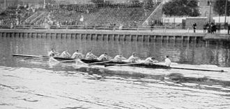 Rowing at the 1912 Summer Olympics – Men's eight - The silver medal winning New College with the wash of the gold medal winning Leander in the foreground.