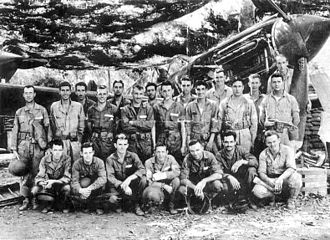 24th Pursuit Group - Group members and one of the last Curtiss P-40Es of the 24th Pursuit Group, taken at Bataan Airfield in early 1942 during the Battle of the Philippines (note Camouflage netting).