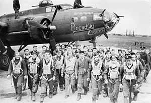 """RAF Great Ashfield -  Bomber crews of the 385th Bomb Group return to base following a mission, they walk past a B-17 Flying Fortress (serial number 42-30251) nicknamed """"Piccadilly Queen""""."""