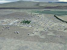 Photo en couleur. Sur un terrain gris apparaissent des petites taches rondes qui forment un groupe.
