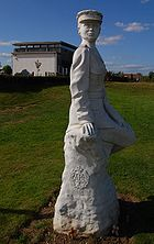 """""""White statue of a woman in uniform, with a chapel in the background."""""""