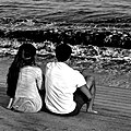 A couple relaxing watching the waves of the Tagus river (25128574951).jpg