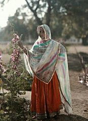 A girl of Agra stands next to a flower bush in traditional clothing by Jules Gervais-Courtellemont.jpg