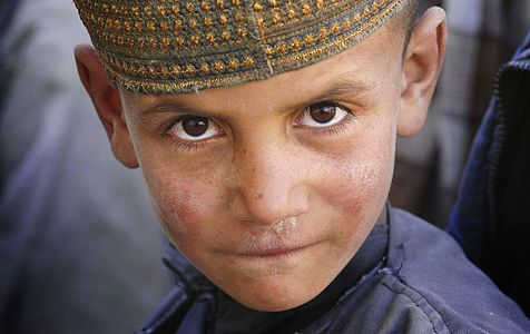 A small boy tries to look mean for the camera in Afghanistan
