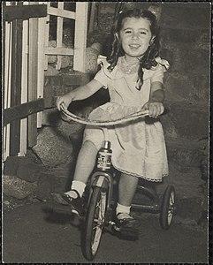 Девушка с локонами и в белом платье на трехколесном велосипеде с треугольником.