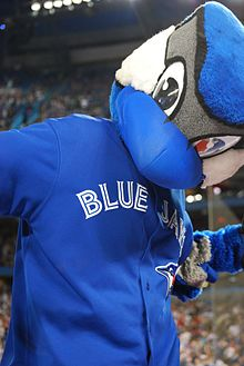 A mascot with a blue jay reminiscent head, and a human body.