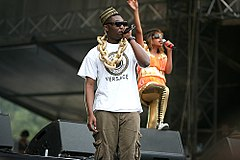 A man wearing an African-style hat, sunglasses, and a large gold chain, and holding a microphone.  In the background a woman in brightly coloured clothing and sunglasses is also holding a microphone and is waving one hand in the air