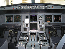 Cockpit of the A330. All instruments and displays are switched on. Two seats occupy both sides of the cockpit, separated by a centre console.
