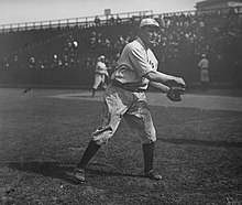 A black-and-white image of a man in a white old-style baseball uniform