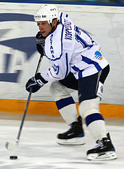 An ice hockey player skating on the ice while using his hockey stick to control the puck. He is wearing a white helmet and a white and black uniform.
