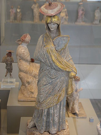 Polychrome - Ancient Greek statue of a woman with blue and gilt garment, fan and sun hat, from Tanagra, 325-300 BC