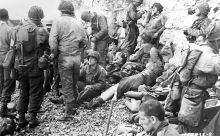 Assault troops of the 3rd Battalion, 16th RCT, from the first two waves, shelter under the chalk cliffs (which identify this as an area of Fox Red). American assault troops at Omaha Beach 02.jpg