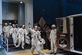 Photographie en couleur des astronautes d'Apollo 11 se rendant au pas de tir en saluant les photographes.