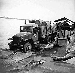 Royal Australian Corps of Transport - AASC Troops near Wewak, New Guinea during WWII using Australian landing craft to transport forward trucks loaded with stores.