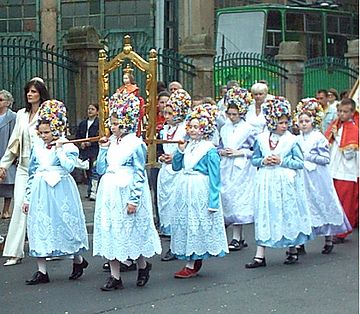 Procession in Poznań, Poland, Corpus Christi 2004. Little girls carrying an Infant Jesus of Prague statue, followed by altar servers clothed in surplice and cassock.