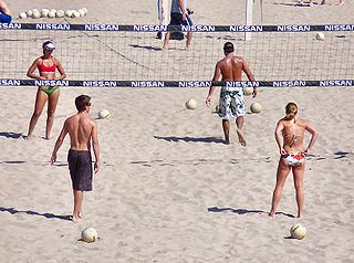 Beach volleyball team sport played by two teams of two players on a sand court divided by a net