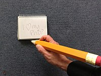 Photograph of a large orange pencil being gripped by the right hand of a man with a notepad nearby