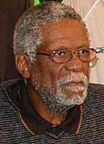 A black bearded elderly man wearing glasses looks toward the right