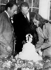 Lauren Bacall cuts their wedding cake, with Bogart and best man Louis Bromfield on her right