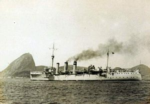 A sleek ship with two funnels is at sea; smoke is streaming to the right