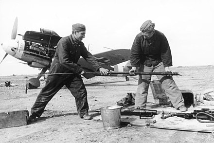 "Marseille's service men, Hoffmann (left) and Berger, cleaning the bore of one of the cannons of a Bf 109. ""Yellow 14"" W.Nr. 8673 can be seen in the background.[43]"