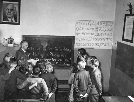 "GDR ""village teacher"", a teacher teaching students of all age groups in one class in 1951 Bundesarchiv Bild 183-13055-0008, Hohendorf, JP mit Dorflehrer.jpg"