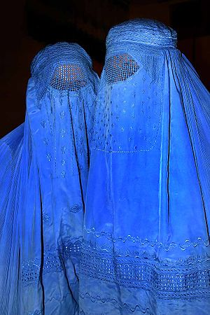 Afghan women wearing their traditional burqas ...
