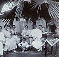 COLLECTIE TROPENMUSEUM Groepsportret tijdens het luisteren naar een grammofoonplaat onder de beschutting van een palmboom TMnr 60053713.jpg