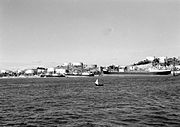 Black and white photograph of three large motor ships docked next to an island covered in large white storage tanks. A small sailboat is visible in the foreground.