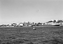 Black and white photograph of three large motor ships docked next to an island covered in large white storage tanks. A small boat is visible in the foreground.