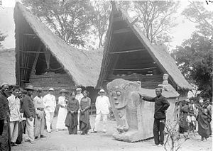 Podom - The kepala negri (head of the village) of Lumban Sui Sui on Samosir standing near a podom, a stone sculpture, in which ancestor skulls are buried circa 1918, photo by Tassilo Adam