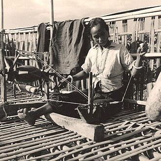 Bandarban District - A Chakma woman weaving on balcony of bamboo house in Bandarban